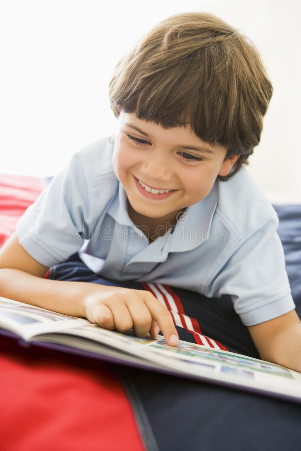Download Young Boy Lying Down On His Bed Reading A Book Stock Image - Image of smiling, down: 6441393