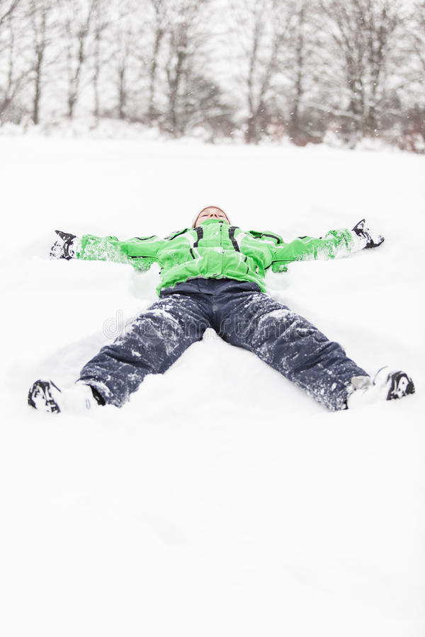 Young boy lying stretched out in the snow royalty free stock images