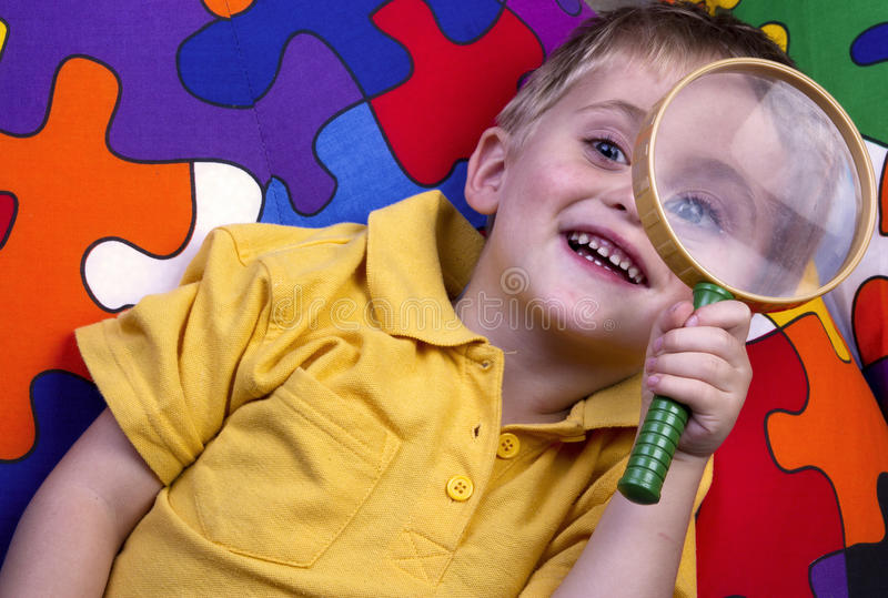 Young boy with magnifying glass stock images