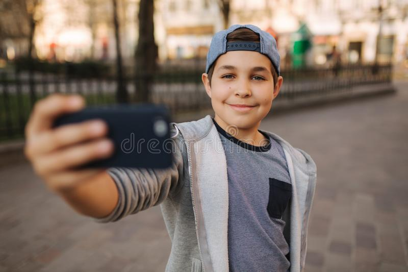 Young boy make a selfie on smartphone in the centre of the city. Cute boy in blue hat. Stylish school boy royalty free stock image