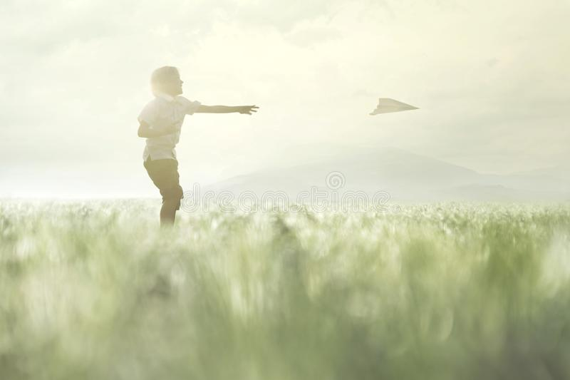 Young boy makes his paper airplane fly in a meadow. Young boy makes his paper airplane fly in the middle of nature royalty free stock photography