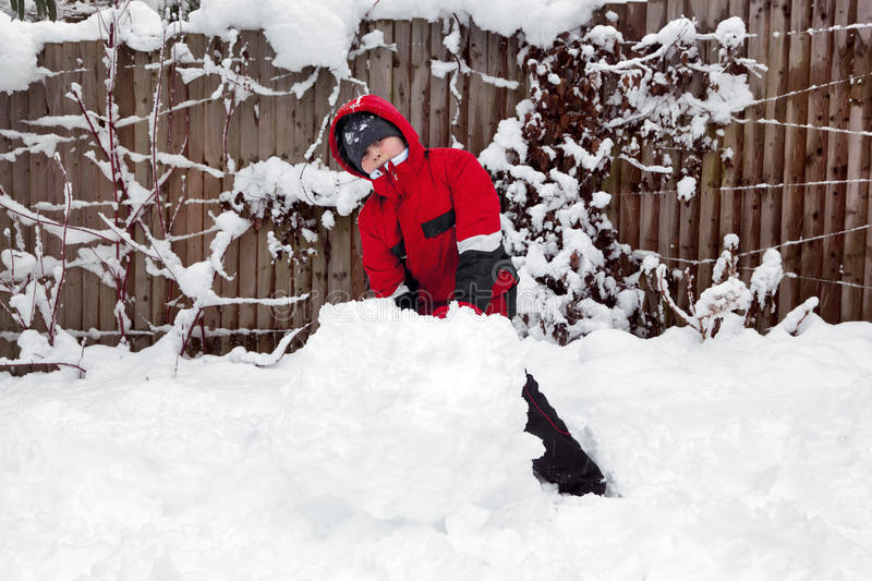 Download Young boy making a snowman stock photo. Image of jacket - 17213358