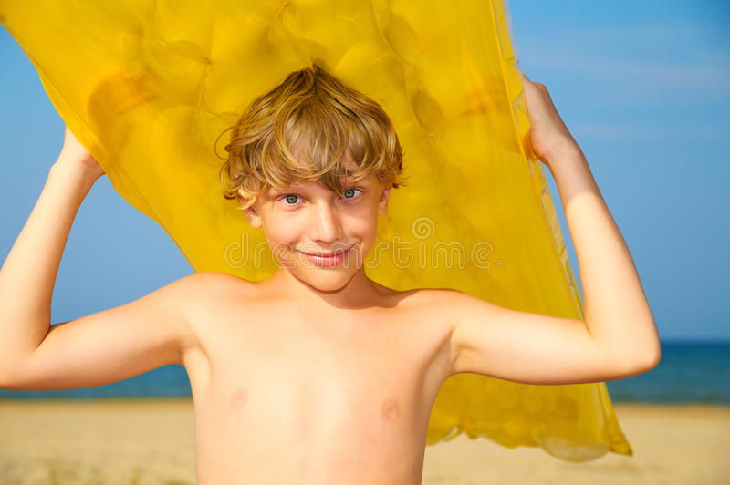 Young boy with mattress on summer beach royalty free stock photo