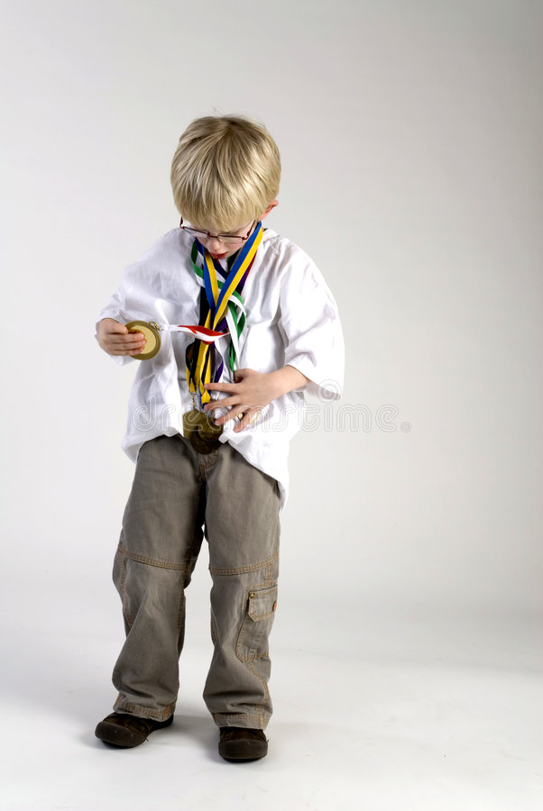 Young boy with medals of honour. A young boy is looking proud to his medals of honour stock photo
