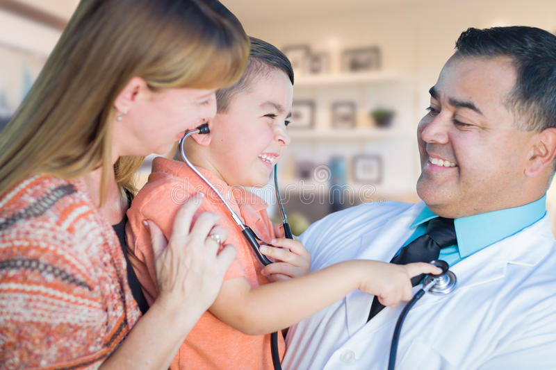 Young Boy and Mother Visiting with Hispanic Doctor in Office.  royalty free stock photo