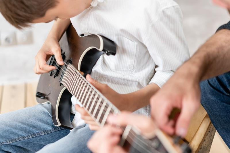 Young boy moves his hand along guitar strings while his father helps boy to take chords royalty free stock photo