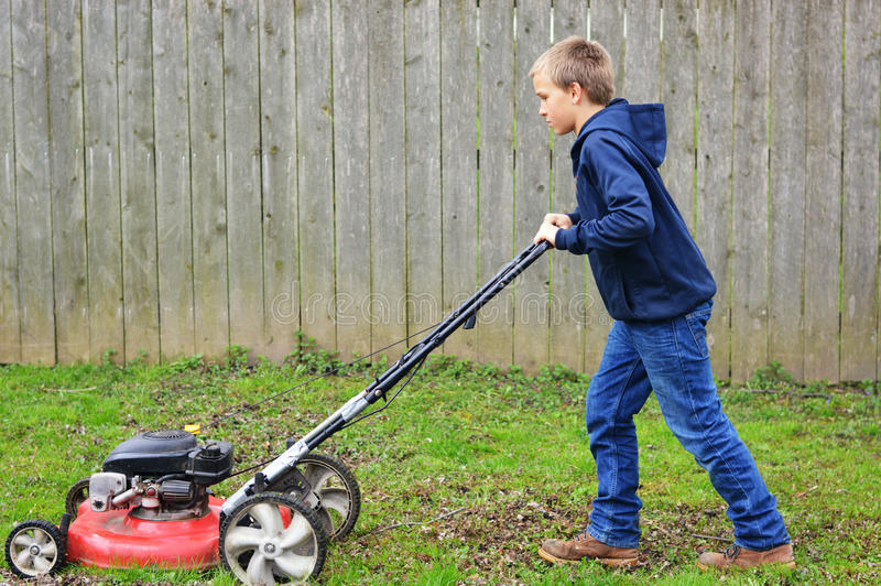 Young Boy Mowing Lawn royalty free stock photos
