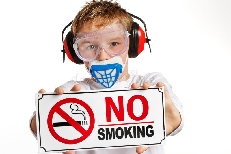 Young boy with no-smoking sign. Boy with ear protection and face mask holding no smoking sign. Shot in the studio against a white background royalty free stock photography