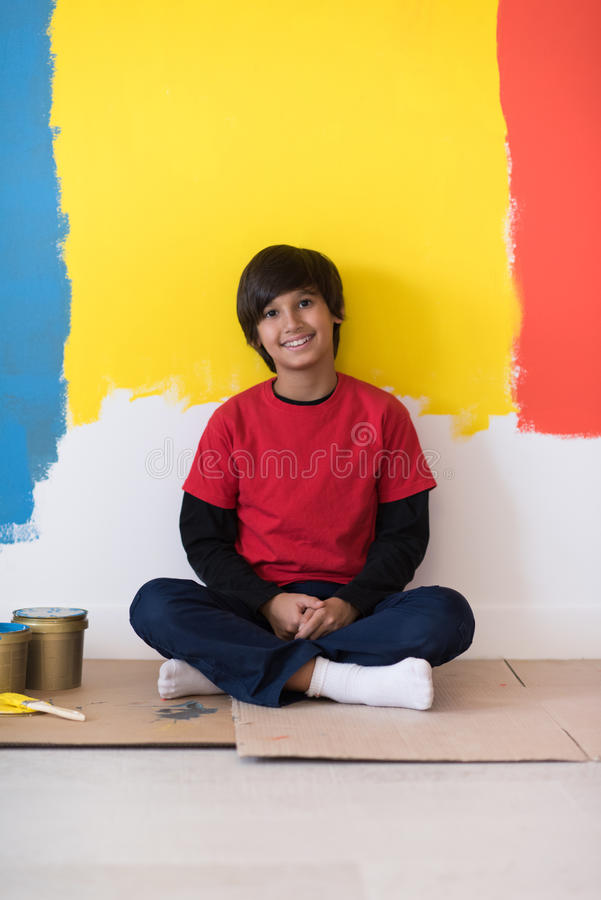 Young boy painter resting after painting the wall stock images