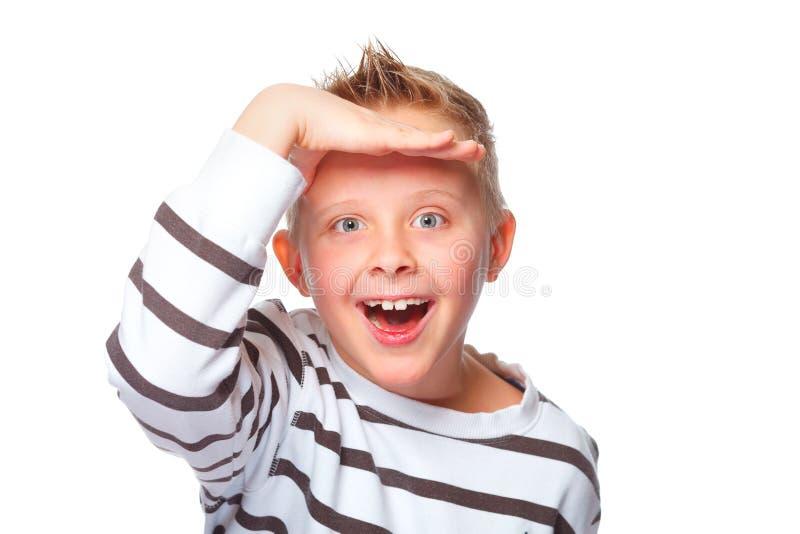 Young boy peeking. Boy peeking with his hand on head stock image