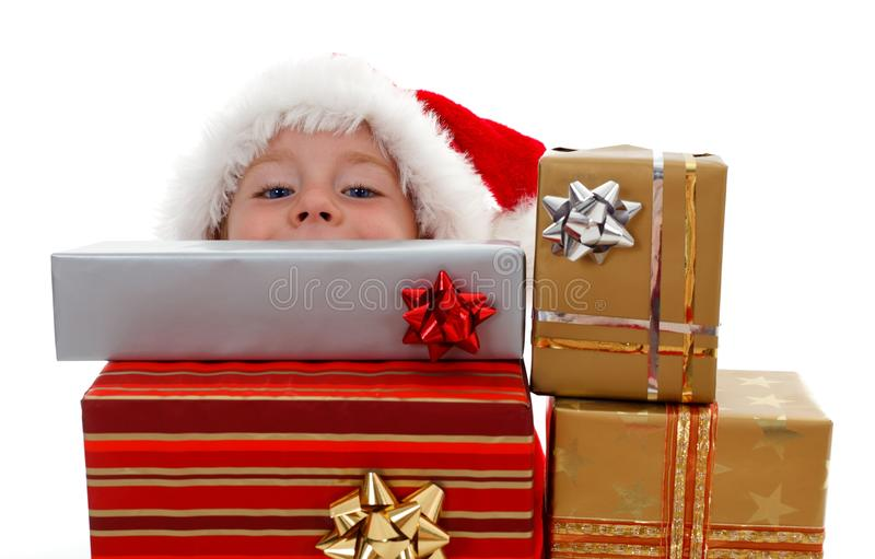 Young boy peeking above gifts. Young boy peeking from behind Christmas presents royalty free stock images
