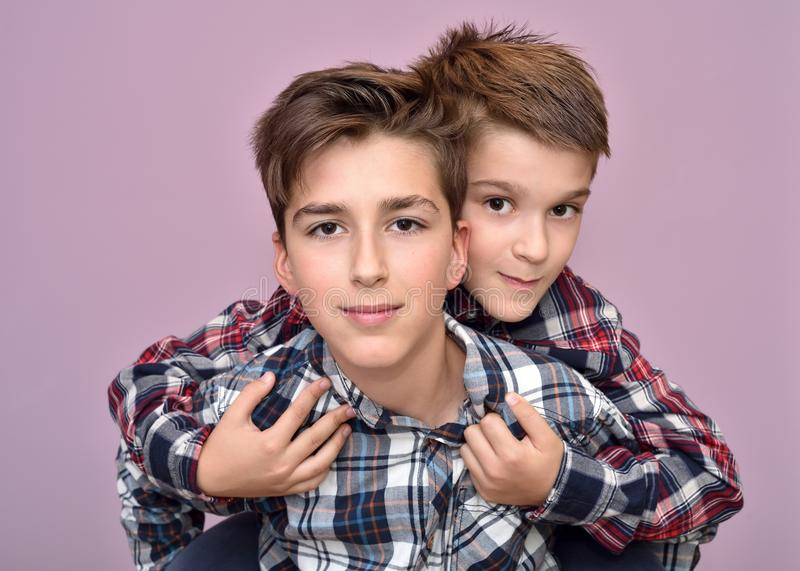Smiling cute brothers. Young boy piggyback riding his little brother royalty free stock image