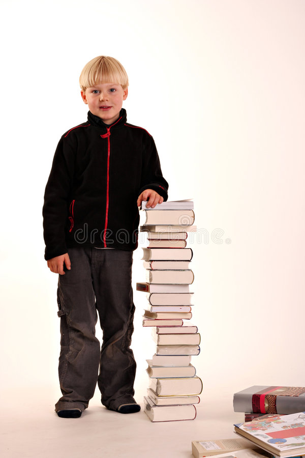 Young boy with a pile of books stock photo