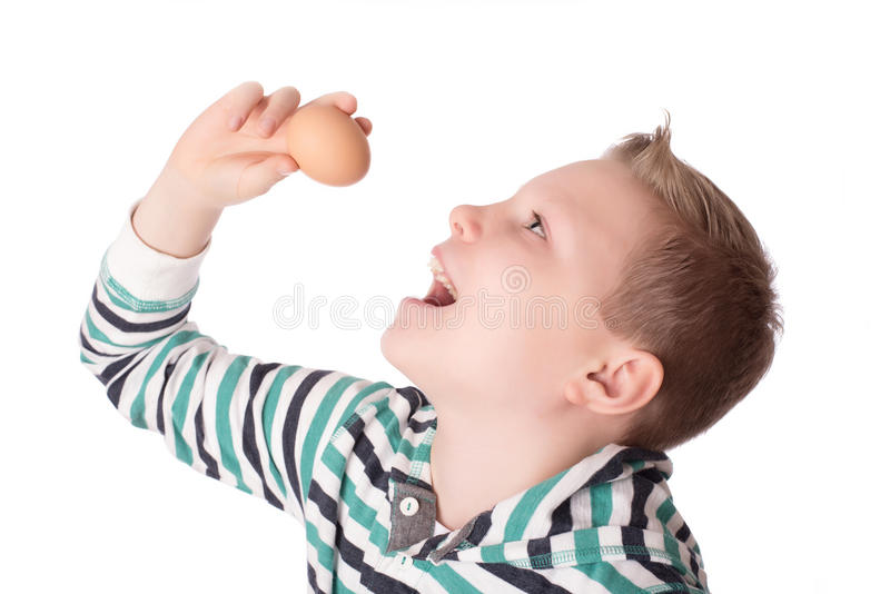Young boy play the eggs over the white. Background stock photo