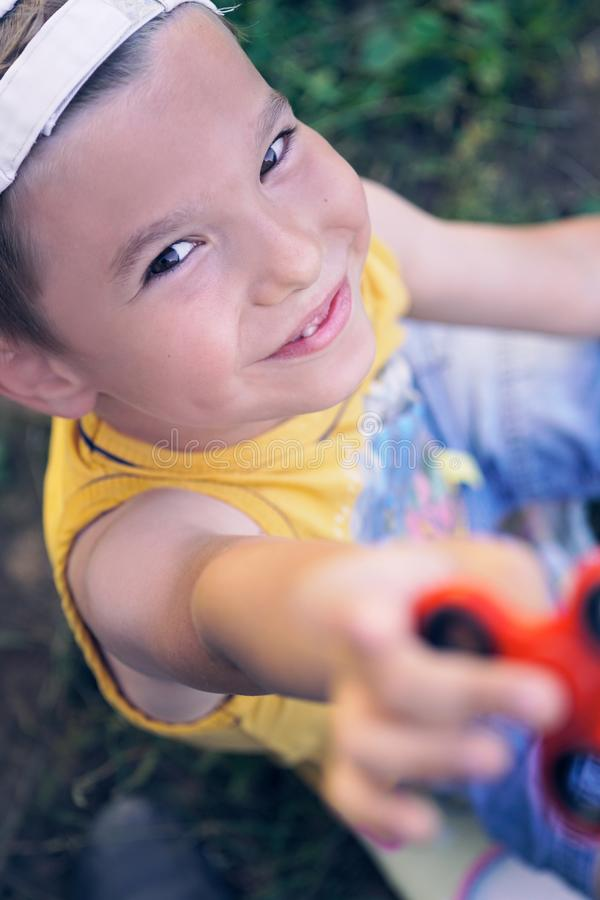 Young boy play with fidget spinner stress relieving toy stock photo