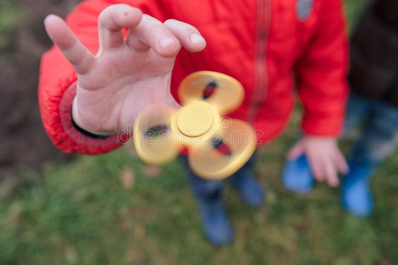 Young boy play with fidget spinner stress relieving toy royalty free stock photo