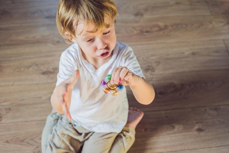 Young boy play with fidget spinner stress relieving toy.  royalty free stock photo