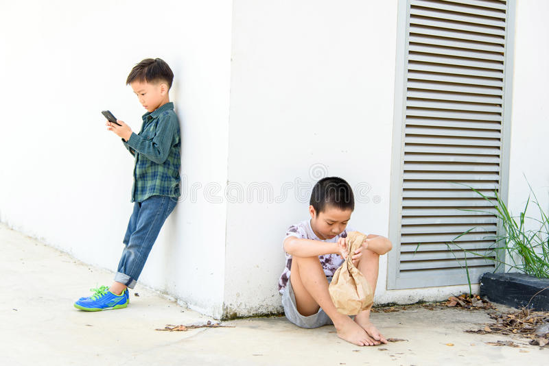 Young boy play smartphone compare with poor boy royalty free stock photo