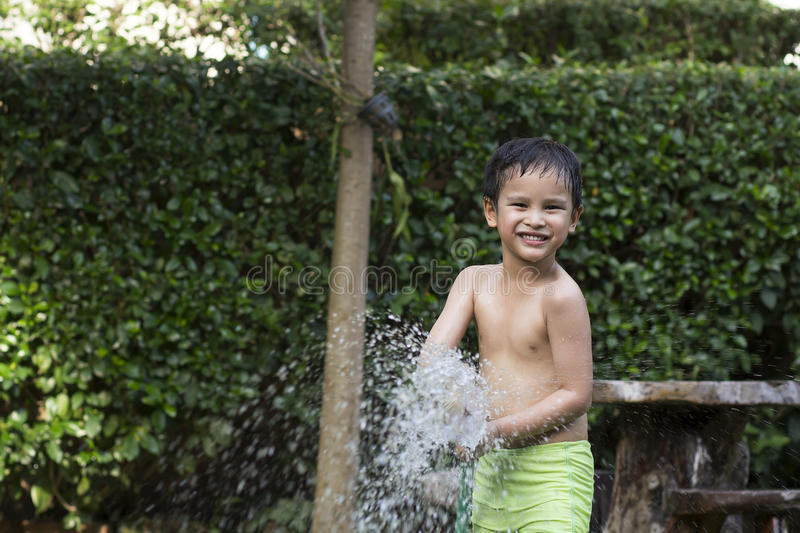 Young boy played water. In gardennnn stock photography