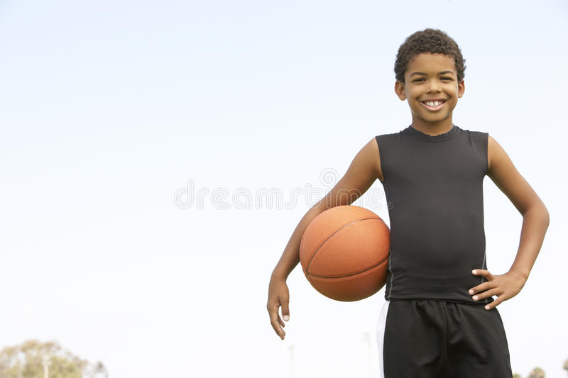 Young Boy Playing Basketball. Smiling To Camera stock image