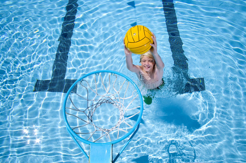 Young boy playing basketball in swimming pool stock photos