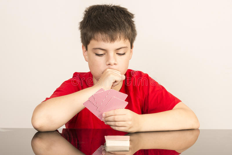 Young boy playing cards stock photos