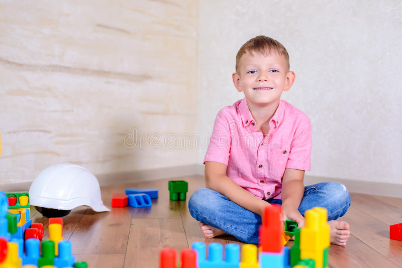Young boy playing with colorful building blocks. Creating a robot and train engine turning to smile at the camera stock image