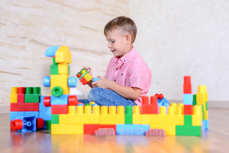 Young boy playing with colorful building blocks. Creating a robot and train engine turning to smile at the camera royalty free stock images