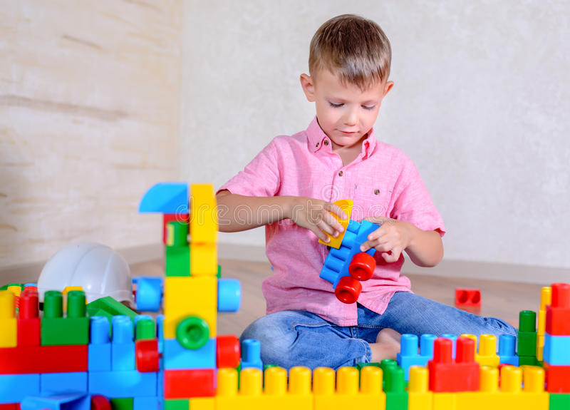 Young boy playing with colorful building blocks. Creating a robot and train engine turning to smile at the camera royalty free stock photos
