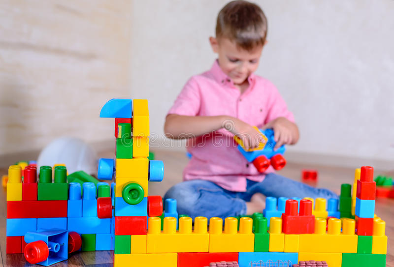 Young boy playing with colorful building blocks. Creating a robot and train engine turning to smile at the camera stock images