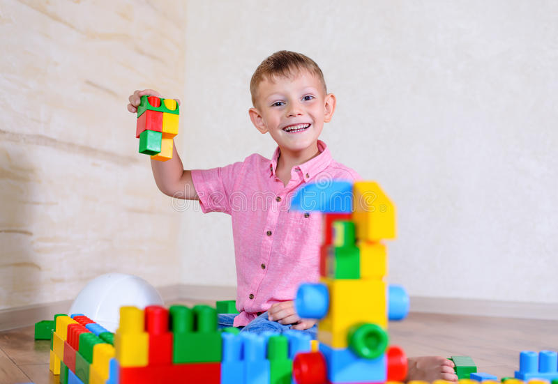 Young boy playing with colorful building blocks. Creating a robot and train engine turning to smile at the camera stock photos
