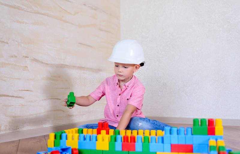 Young boy playing with colorful building blocks. Young boy playing with colorful plastic interlocking building blocks wearing a hardhat as he pretends to be a royalty free stock photography