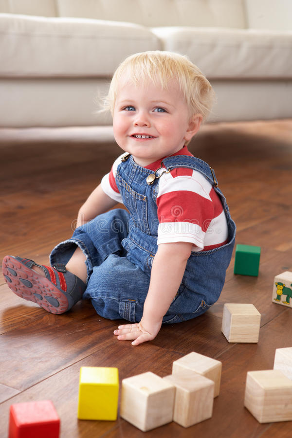 Young Boy Playing With Coloured Blocks At Home royalty free stock images
