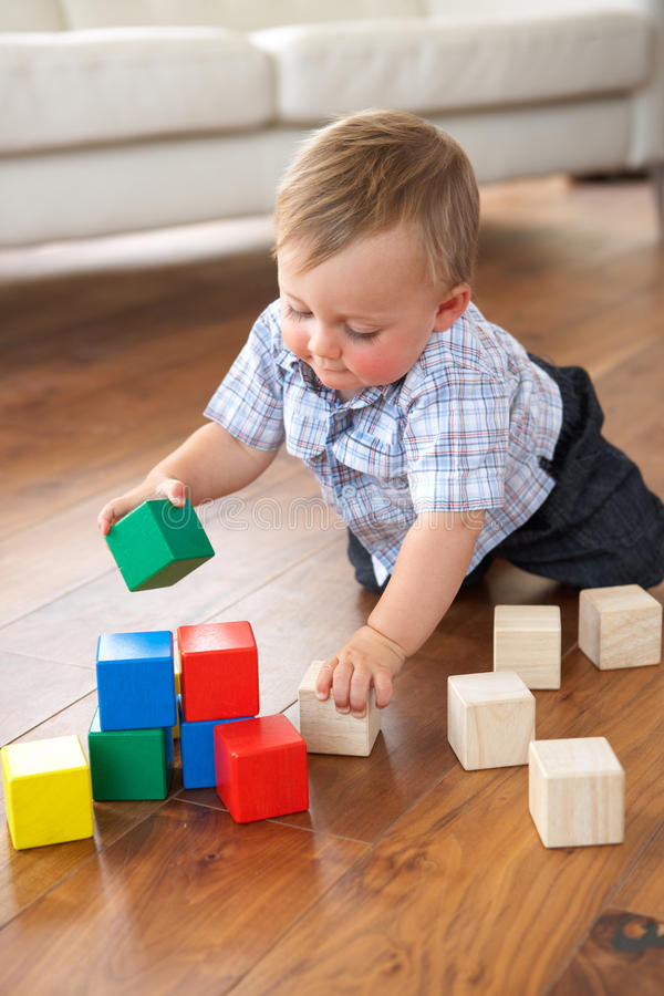 Young Boy Playing With Coloured Blocks At Home stock photo