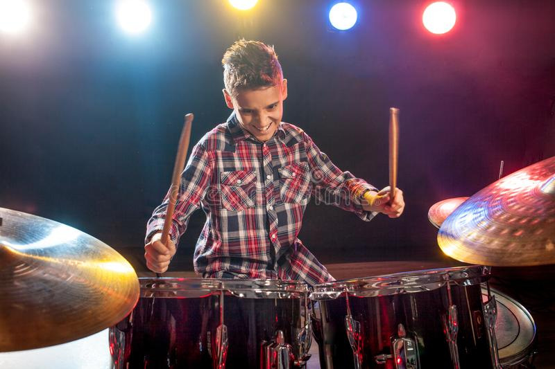 Young boy playing drums. Happy young boy playing drums royalty free stock image