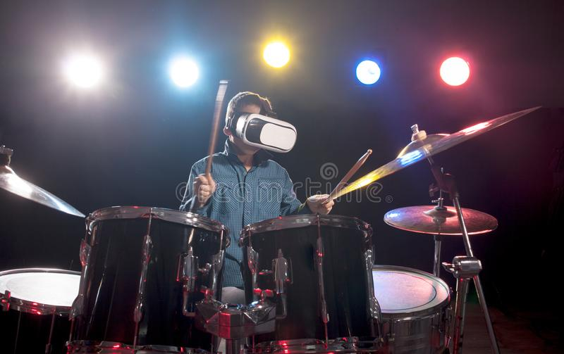 The boy learns to play drums, with glasses for virtual reality. Young boy playing drums using viewer for virtual reality stock photos