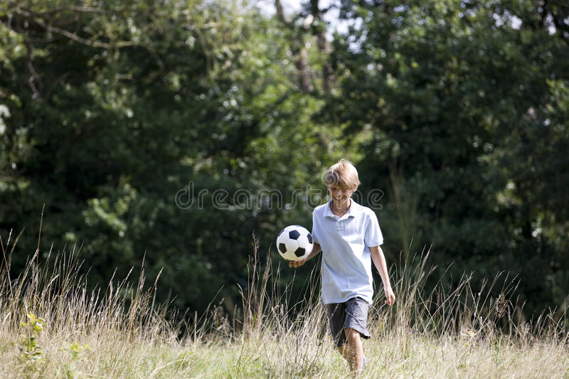 A young boy playing football in a field royalty free stock image
