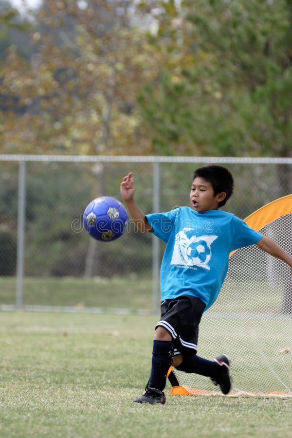 Young boy playing goalie with a big kick stock image