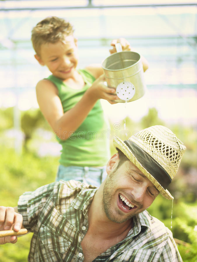 Young boy playing with his father in a green house stock photos
