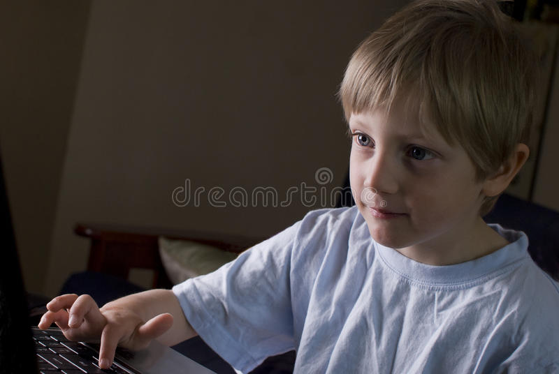 Young Boy playing on laptop stock photos