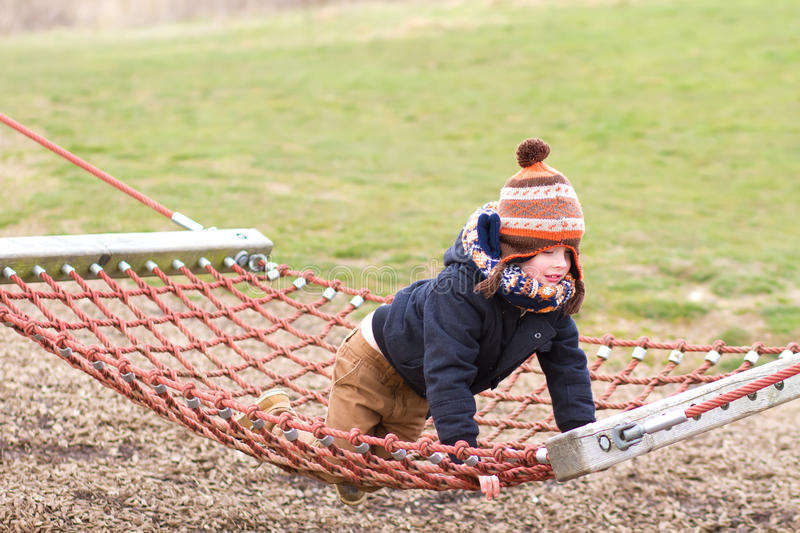 young boy playing at the park on a cold day stock images