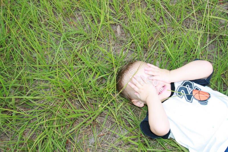 Young boy playing Peek a Boo stock photo