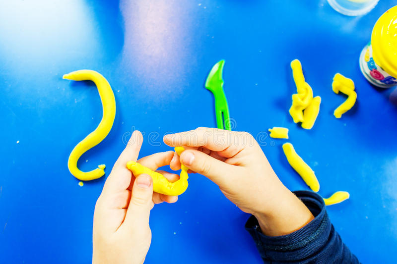 Young boy is playing with plasticine. On blue table with many colors of modeling clay stock images