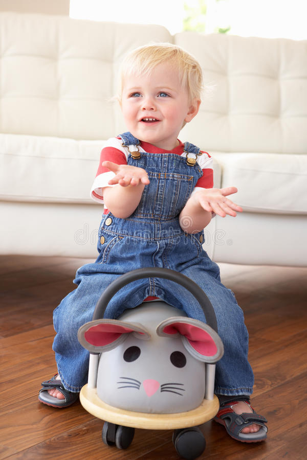 Young Boy Playing With Ride On Toy Mouse At Home royalty free stock photo