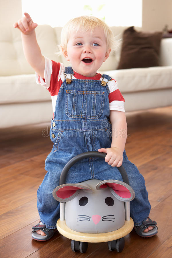 Young Boy Playing With Ride On Toy Mouse At Home stock photography