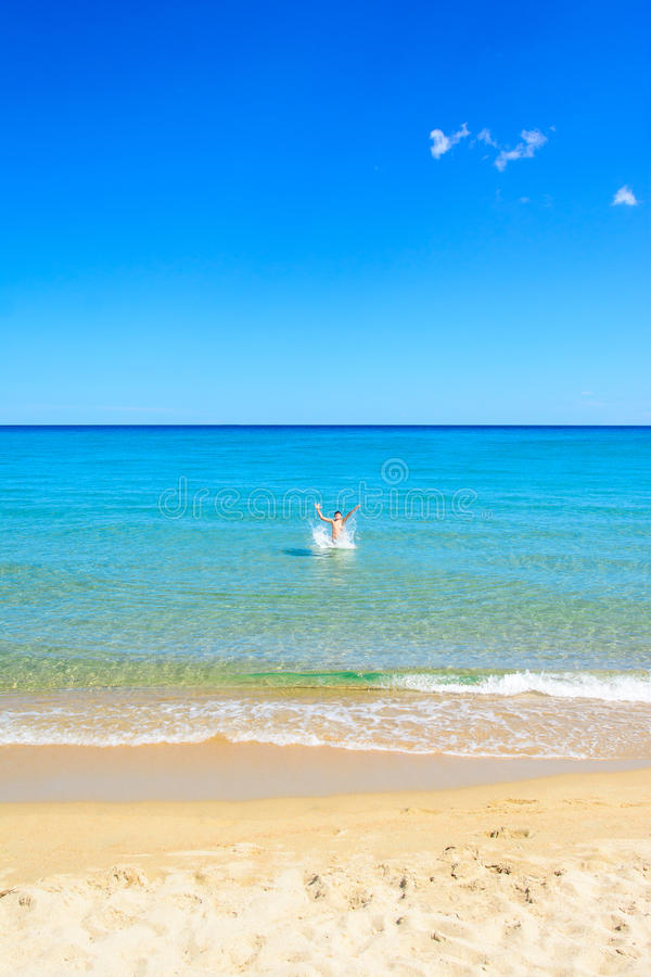 Young boy playing into the sea stock photography
