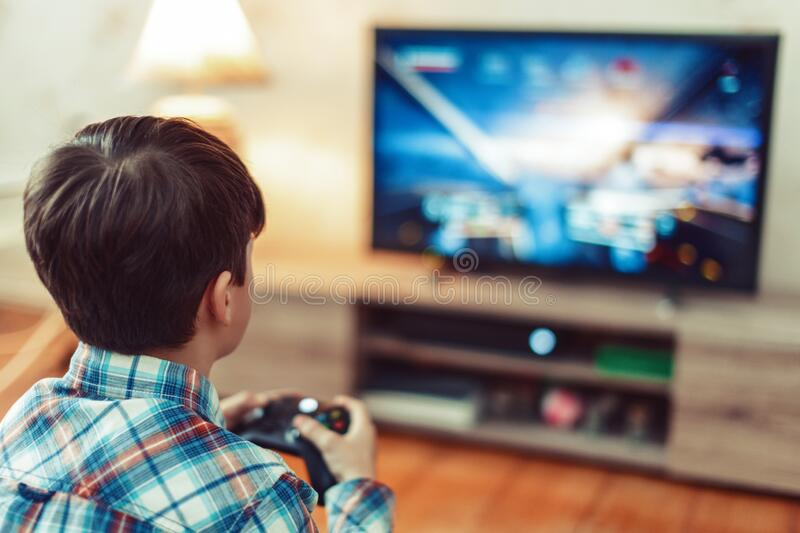 Young boy playing video game on console by controller stock photography