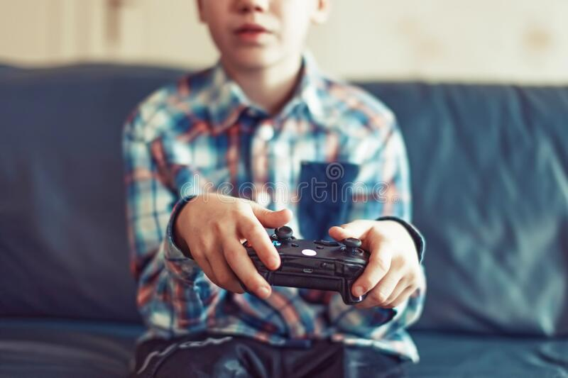 Young boy playing video game by controller closeup royalty free stock photo