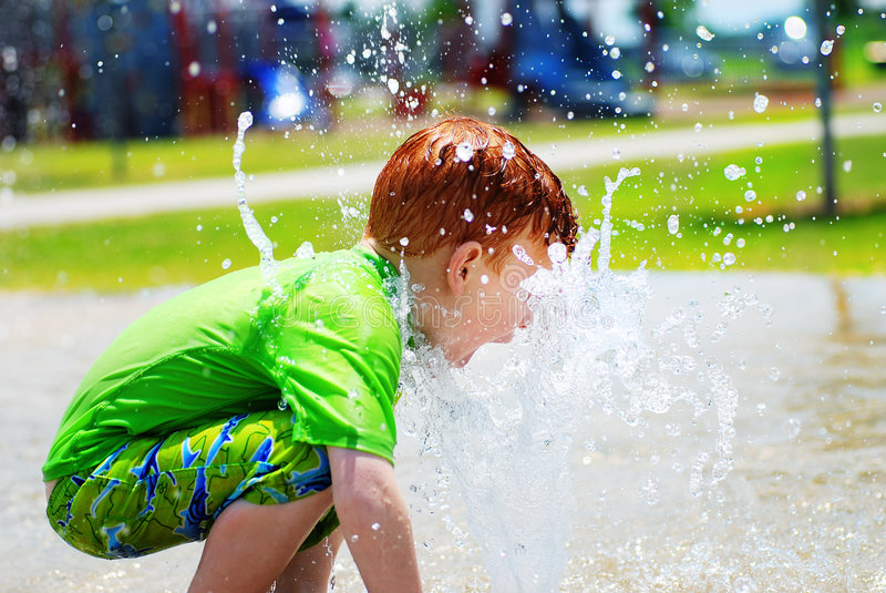 Young boy playing in water stock photography