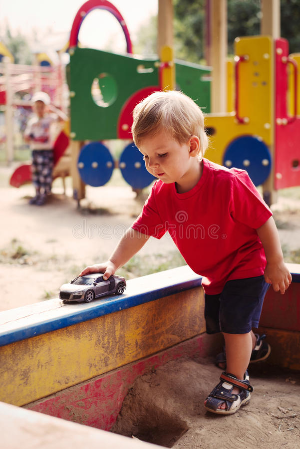 Free Young Boy Playing With Toy Car In Sandbox Stock Image - 44024931